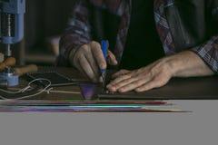 Lederner Hersteller schnitt Leder mit Gebrauchsmesser und Machthaber auf speziellem Stand Stockbild