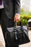 Lederner Koffer in der Hand Person in der Klage, die Manntasche hält stockfoto