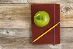 Lederner Notizblock mit Apfel und Bleistift für Schule oder Büro auf ru Lizenzfreie Stockfotografie
