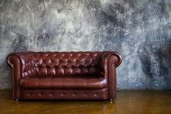 Ledernes braunes Sofa im städtischen Dachbodeninnenraum Stockfotos