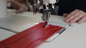 Ledernes Nähen mit einer Nähmaschine Isolat über Weiß stock footage