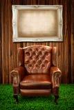 Ledernes Sofa auf Feld des grünen Grases und des Fotos Stockbilder
