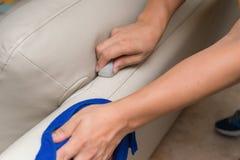 Ledernes Sofa der Reinigung mit Schwamm und Tuch Stockfotografie