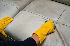 Ledernes Sofa der Reinigung zu Hause mit nassem Tuch Stockfotos