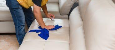 Ledernes Sofa der Reinigung zu Hause mit Schwamm u. Tuch Stockfotos