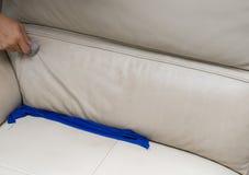 Ledernes Sofa der Reinigung zu Hause mit Schwamm u. Tuch Lizenzfreie Stockbilder