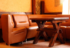 Ledernes Sofa und hölzerne Tabelle Stockfotografie