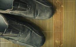 Lederschuhe auf der Matte Stockfotos