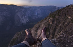 Lederschuhe, die weg von einer Klippe hängen Lizenzfreies Stockfoto