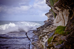 Ledge at the base of coastal cliffs. Waves breaking on a rocky ledge at the base of steep coastal cliffs Royalty Free Stock Photography
