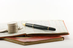 Ledgers Money Pen. Two financial ledgers and a pile of coins on a white background Stock Images