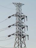 Ledningsförmåga till elektricitetspoler och hus Arkivfoto