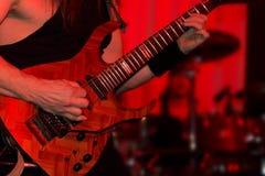 Ledningsgitarrist som spelar den elektriska gitarren i en musikband Arkivbild