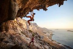 Ledningsklättring för ung kvinna i grotta royaltyfri fotografi