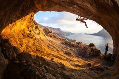 Ledningsklättring för ung kvinna i grotta Royaltyfri Bild