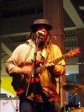 Ledningssångaren av vägledningsmusikbandet sitter fast på gitarren på etapp på Mai Tai Arkivfoton
