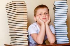 Ledsen åtta-år-gammal pojke och många böcker på tabellen royaltyfri fotografi