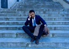 Ledsen affärsman som lider från fördjupning i sammanlagd förtvivlan som är hopplös och som är frustrerad i stadstrappa arkivfoto