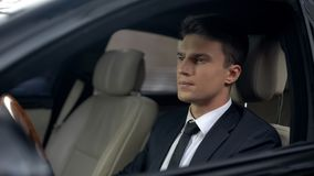Ledsen affärsman som sitter på bilen i underjordisk parkering som förbereder sig för arbete royaltyfria bilder