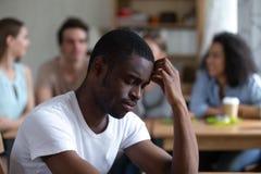 Ledsen afrikansk amerikanman som lider från att trakassera eller rasdiskriminering arkivfoto