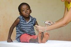 Ledsen afrikansk pojke som är klar att få en injektion från en volontärsjuksköterska i Bamako, Mali arkivbild