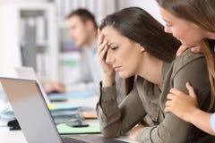 Ledsen anställd som tröstas av en kollega arkivbild