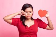 Ledsen asiatisk kvinna och skrik med r?d hj?rta royaltyfri bild