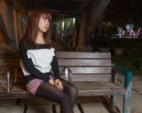 Ledsen asiatisk kvinna på en parkerabänk Royaltyfri Foto