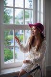 Ledsen asiatisk tappningkvinna på fönstret Royaltyfria Foton