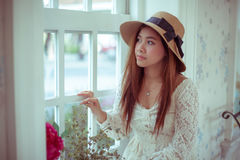Ledsen asiatisk tappningkvinna på fönstret Arkivfoton