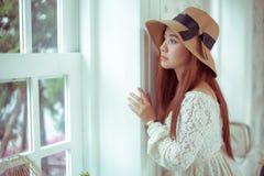 Ledsen asiatisk tappningkvinna på fönstret Royaltyfri Fotografi