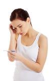 Ledsen bekymrad kvinna med graviditetstestet. Arkivbild