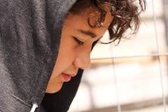 Ledsen besvärad latinamerikan 13 år tonåring för pojke för gammal skola som bär posera för hoodie som är utomhus- - nära övre royaltyfri foto