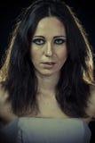 Ledsen brunettkvinna med den långa hår och aftonkappan royaltyfri foto