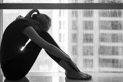 Ledsen deprimerad kvinna som gråter i hennes regniga dag för sovrumduringummin arkivfoto