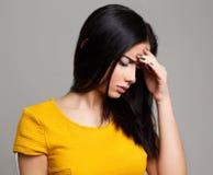 Ledsen deprimerad kvinna som har huvudvärk Arkivbild