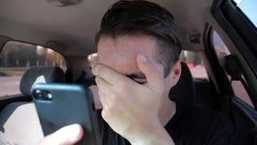 Ledsen desperat man som läser dåliga sms på smatphonegråt i bilen lager videofilmer