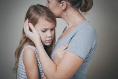 Ledsen dotter som hemma kramar hans moder Royaltyfri Fotografi