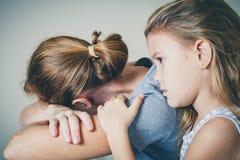 Ledsen dotter som kramar hans moder fotografering för bildbyråer