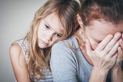 Ledsen dotter som kramar hans moder Arkivfoton