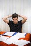 Ledsen eller bekymrad ung man som arbetar eller studerar på Arkivfoto