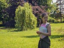 Ledsen ensam caucasian tonårs- flicka i parkera som omges av träd på bakgrunden royaltyfria foton