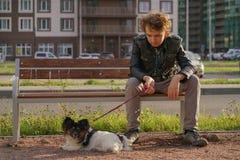 Ledsen ensam grabb som sitter p? en b?nk med hans hund sv?righeterna av ton?rstid i kommunikationsbegrepp arkivfoton