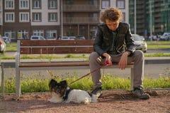 Ledsen ensam grabb som sitter p? en b?nk med hans hund sv?righeterna av ton?rstid i kommunikationsbegrepp royaltyfri foto