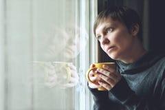 Ledsen ensam kvinna som dricker kaffe i mörkt rum Arkivfoto