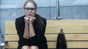 Ledsen ensam kvinna som sitter på bänken som är trött av rusning av stadsfördjupningen lager videofilmer