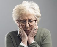 Ledsen ensam ?ldre kvinna som poserar med huvudet i h?nder arkivbild