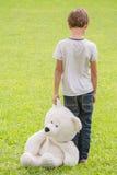 Ledsen ensam pojke med nallebjörnen som står i ängen Barn som ner ser tillbaka sikt Sorgsenhet skräck, ensamhetbegrepp arkivbilder