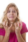 Ledsen flicka i förtvivlan över vit bakgrund Arkivbild