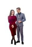 Ledsen flicka i röd klänning och förbittrad grabb arkivfoto